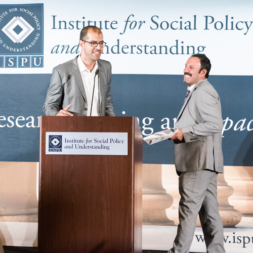 Two men enthusiastically greet each other at the podium during an event