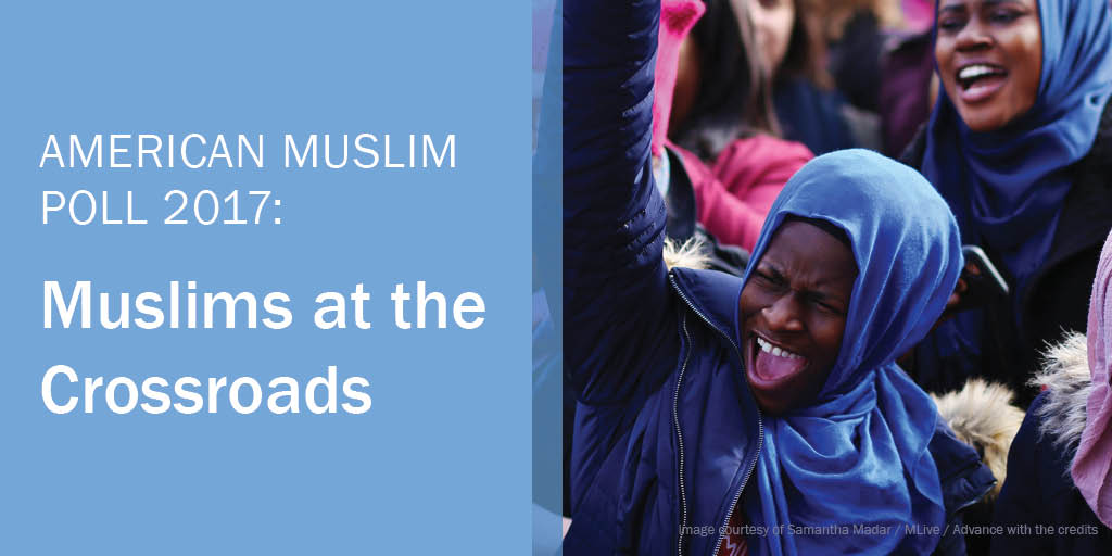 American Muslim Poll 2017: Muslims at the Crossroads. A Muslim woman in a blue hijab raises her fist in the air at a rally.