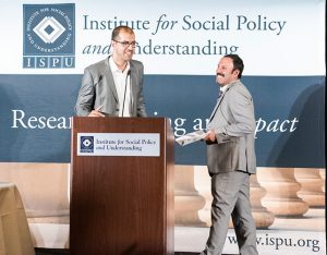 Two men enthusiastically greet each other at a podium during an event