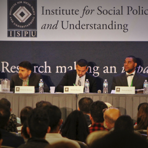 A panel of 5 experts address a large crowd of people.
