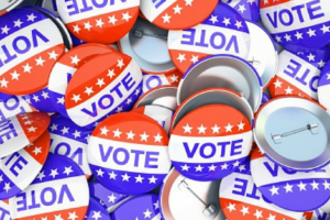 A pile of red, white, and blue VOTE pins