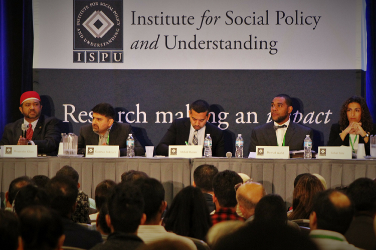 A panel of 5 experts address a large crowd