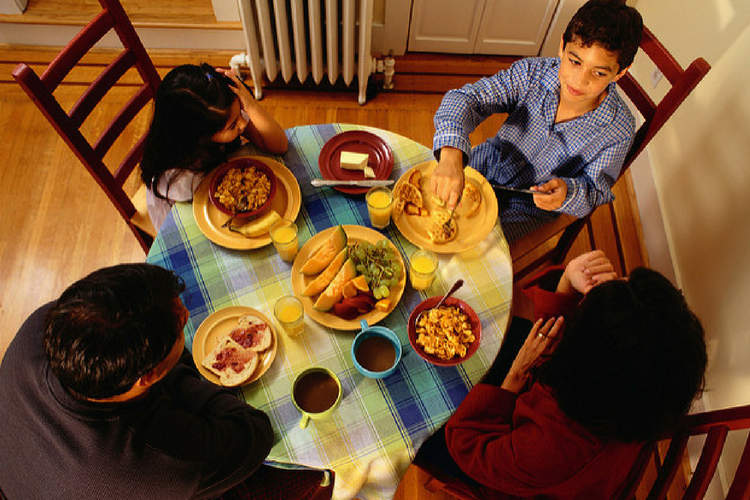A family with young children sitting around a table eating breakfast