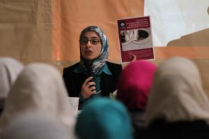 ISPU Scholar and report author Amal Killawi holding up a marriage and divorce report in front of a group of Muslim women