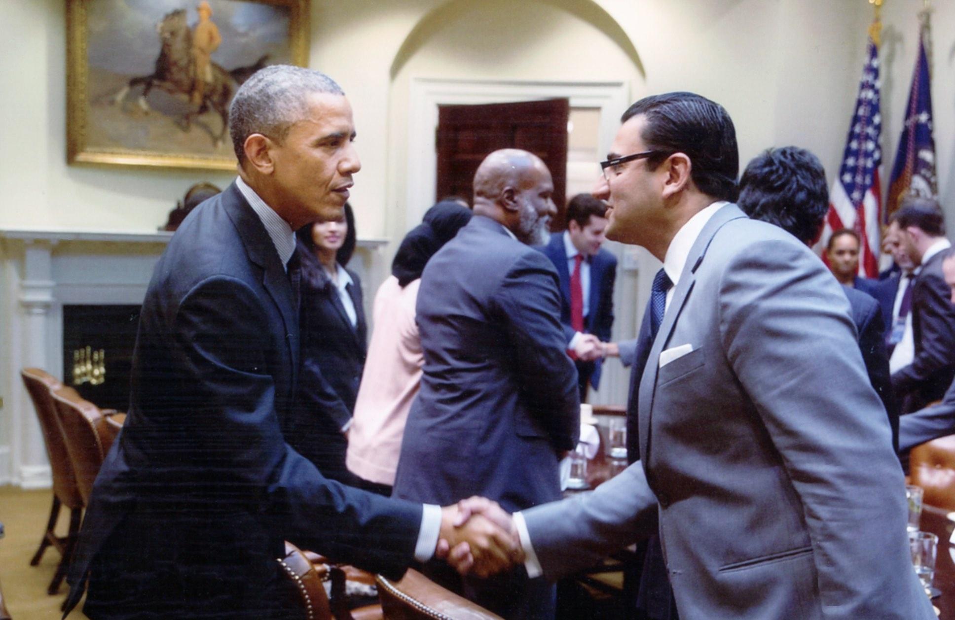 Former President Barack Obama shaking hands with Farhan Latif