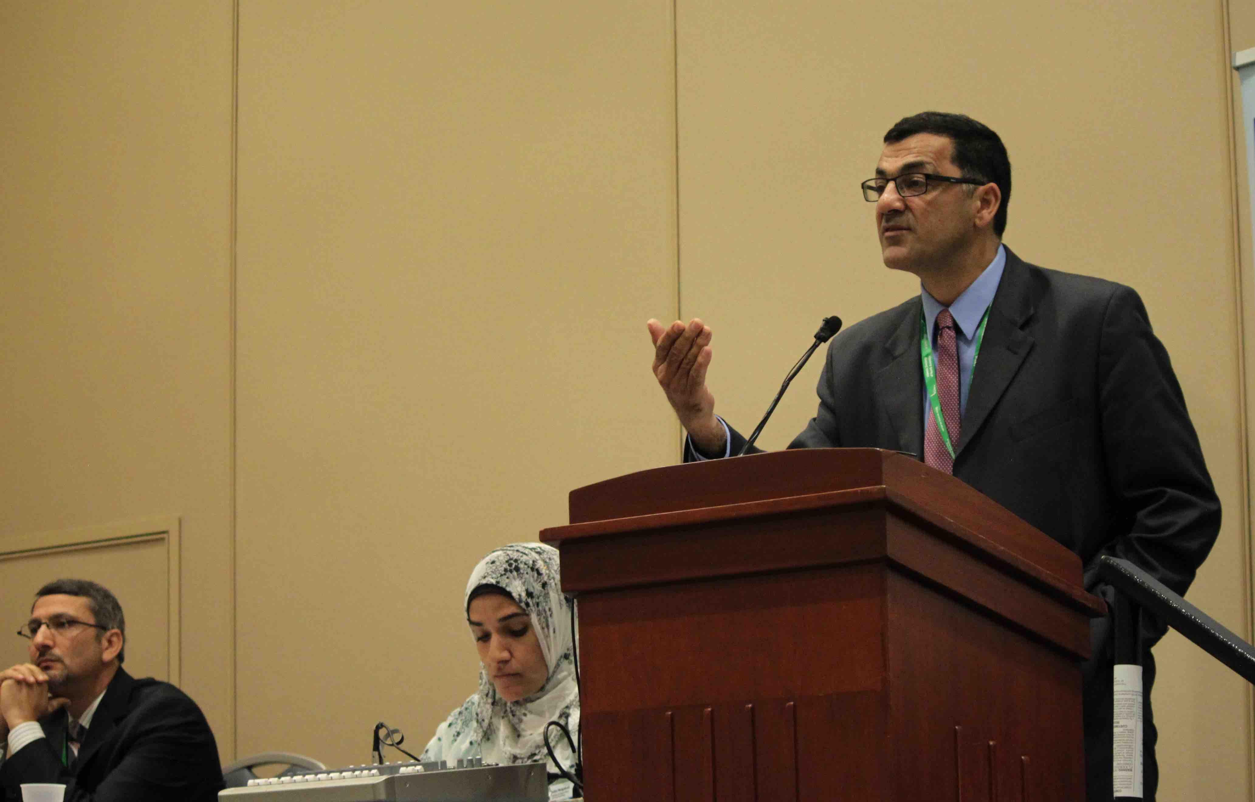 Debate participant Salam Al-Marayati at the podium explaining his perspective