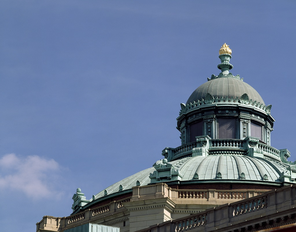 The top of the dome of the Library of Congress - a intricate green cooper room with a statue of a torch at the very top