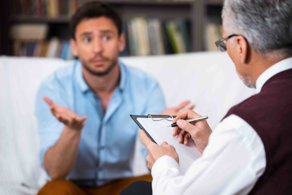 A serious young man sits across from his gray-haired therapist, who is holding a clipboard