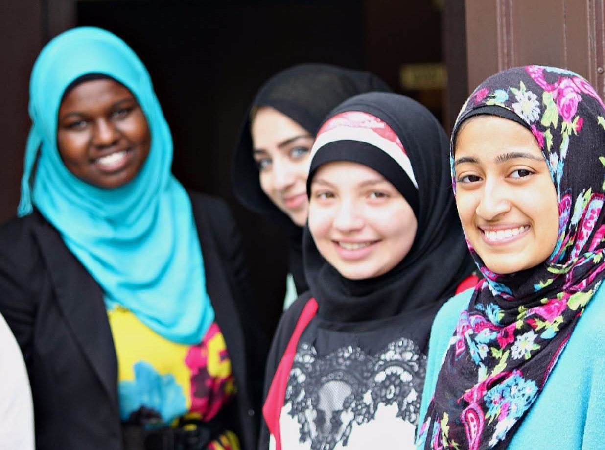 Four young, Muslim women smiling at the camera