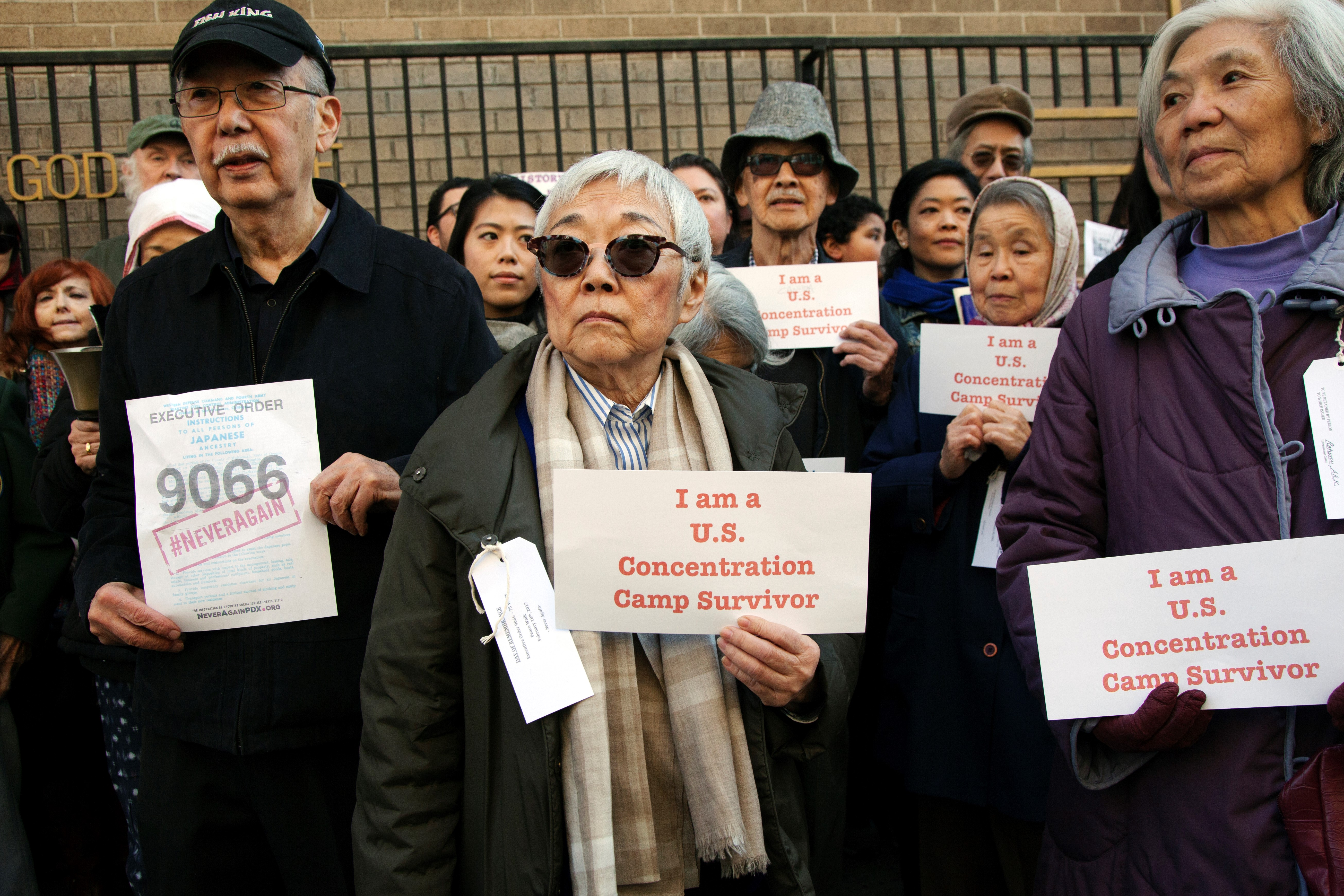 """A group of survivors of Japanese internment camps hold signs reading """"I am a U.S. Concentration Camp Survivor"""""""