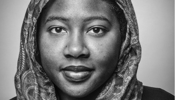A black and white photo of woman wearing a patterned hijab. She looks straight into the camera.