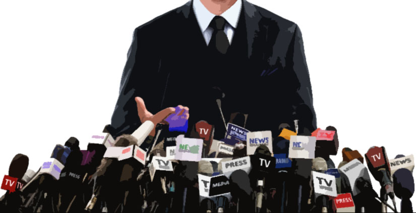 A man in a suit in front of an array of news organizations' microphones during a press conference