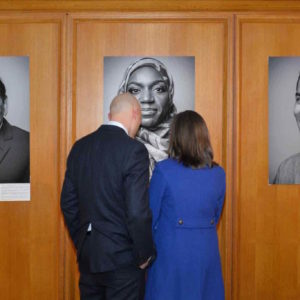 2 people looking at a photo narrative exhibit.