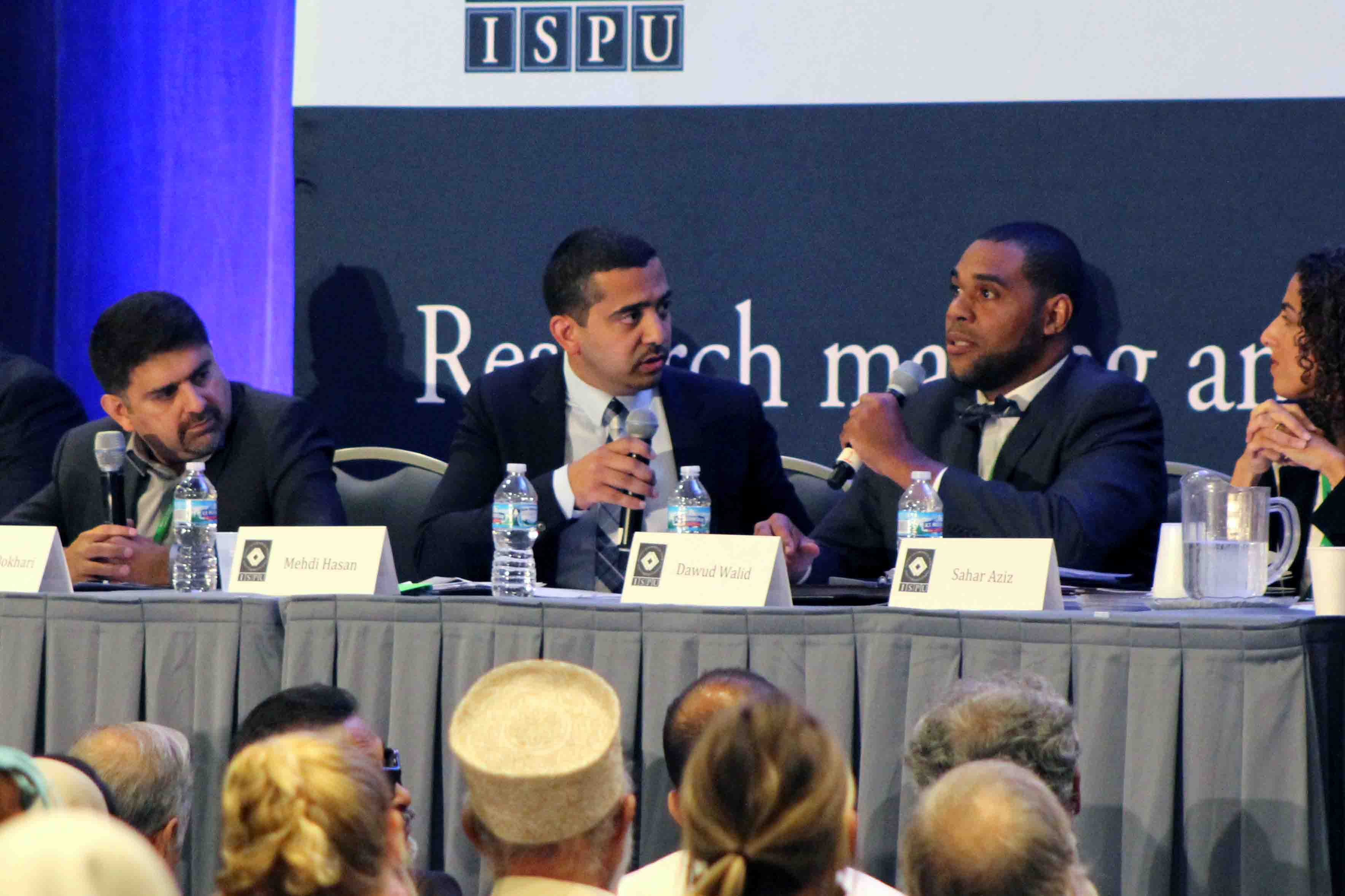 A panel of debaters with microphones facing a crowded room