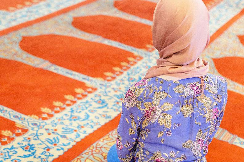A hijabi woman kneeling on a prayer rug