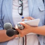 A journalist holding a recorder and two microphones while writing in a notepad