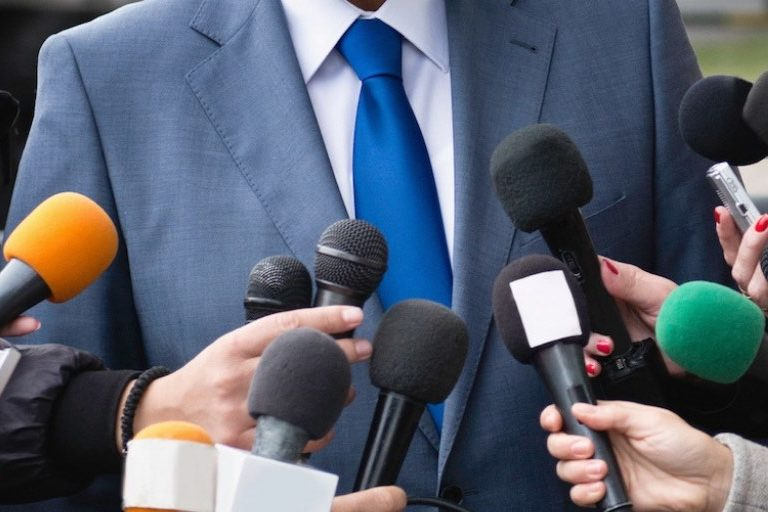 A man in a suit is surrounded by reporters with microphones