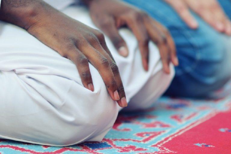 two men kneeling on prayer rug