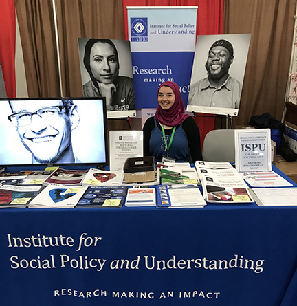 A young woman wearing a hijab behind a booth filled with reports