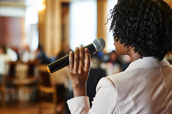 Female speaker with microphone giving presentation