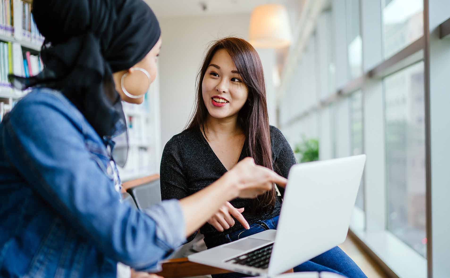 A young Asian woman has a business meeting with a Muslim woman. They are both sitting in an office and talking over a laptop computer during the day