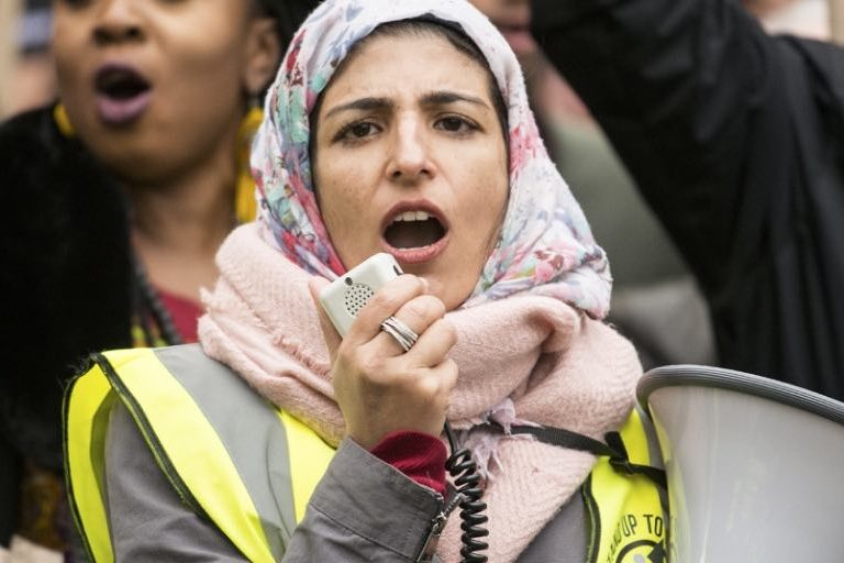 A woman wearing a hijab speaks in to a megaphone at a protest