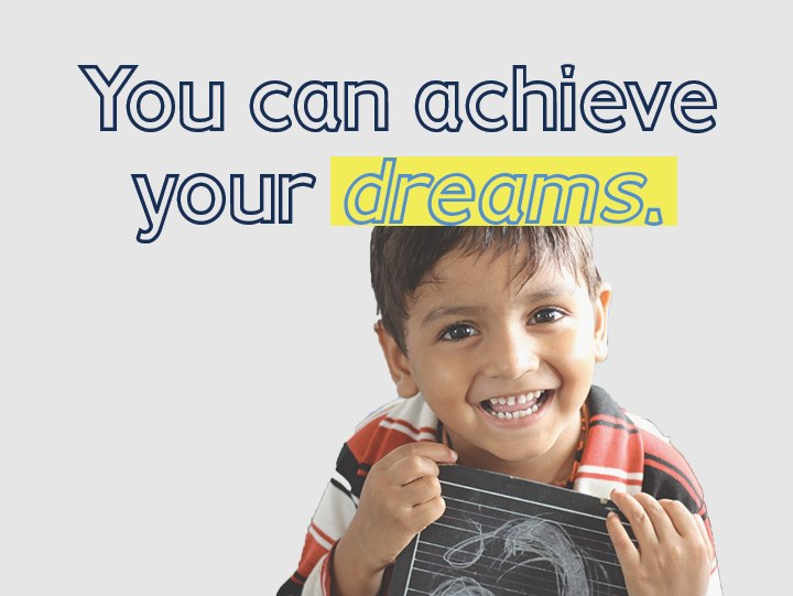 """""""You can achieve your dreams."""" A photo of a smiling young boy holding a small chalk board"""