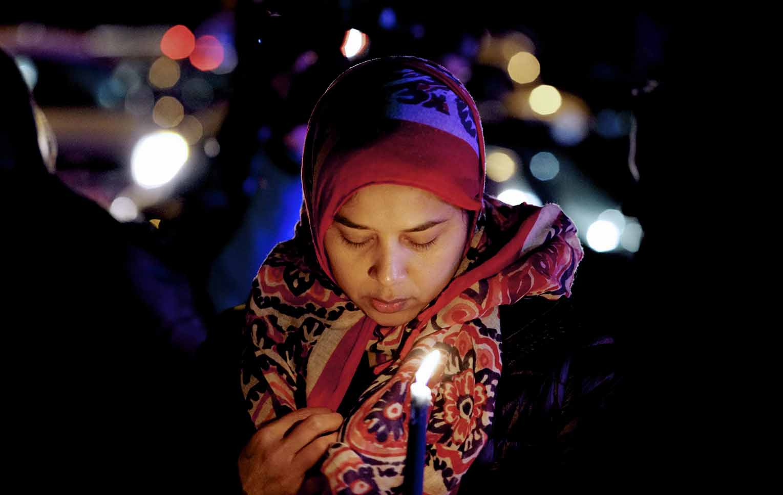 A Muslim woman at a vigil holds a candle and bows her head