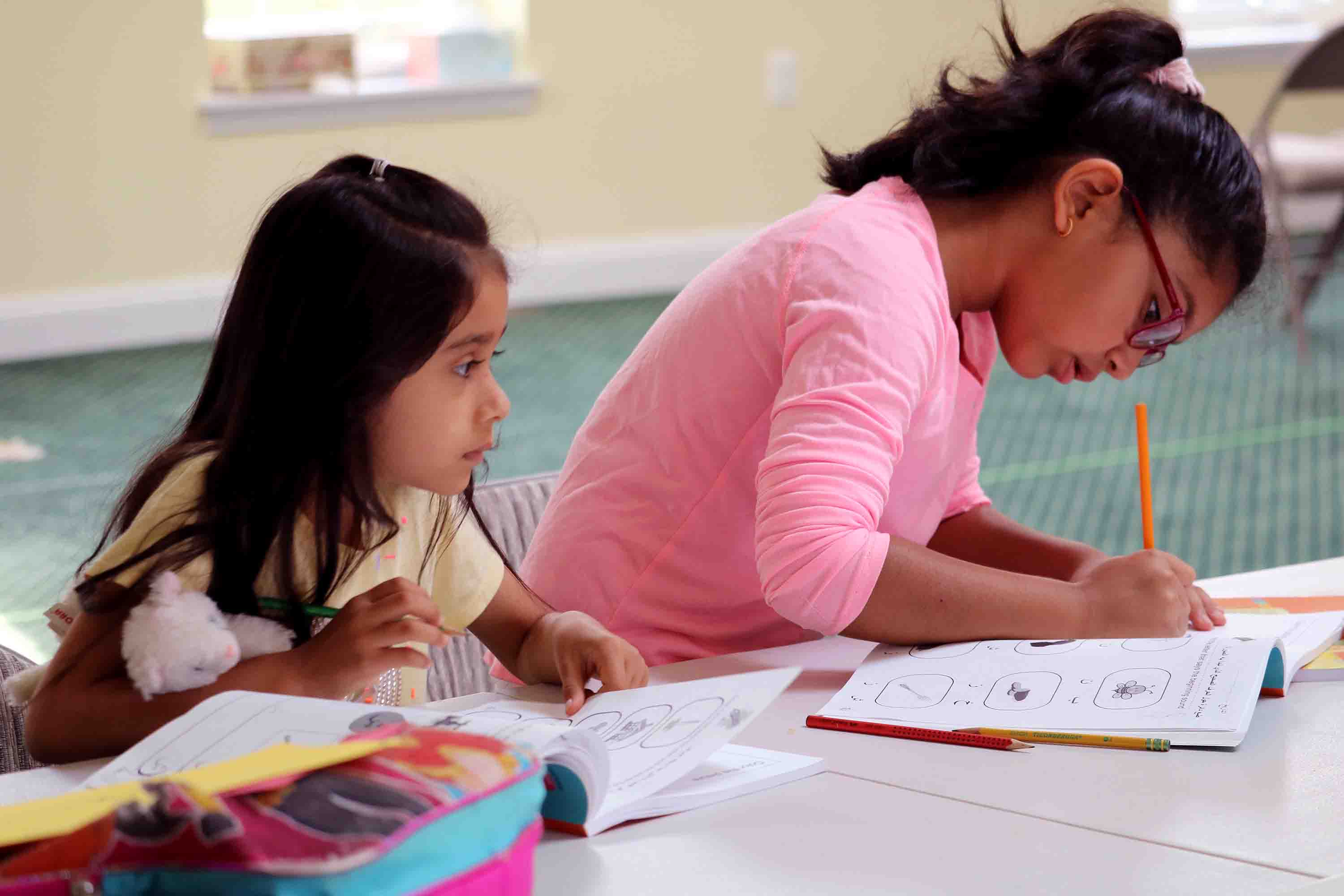 Two young girls complete assignments in workbooks
