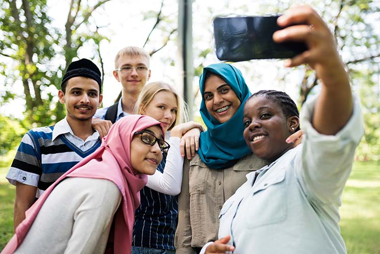 A diverse group of kids gathers around to take a selfie