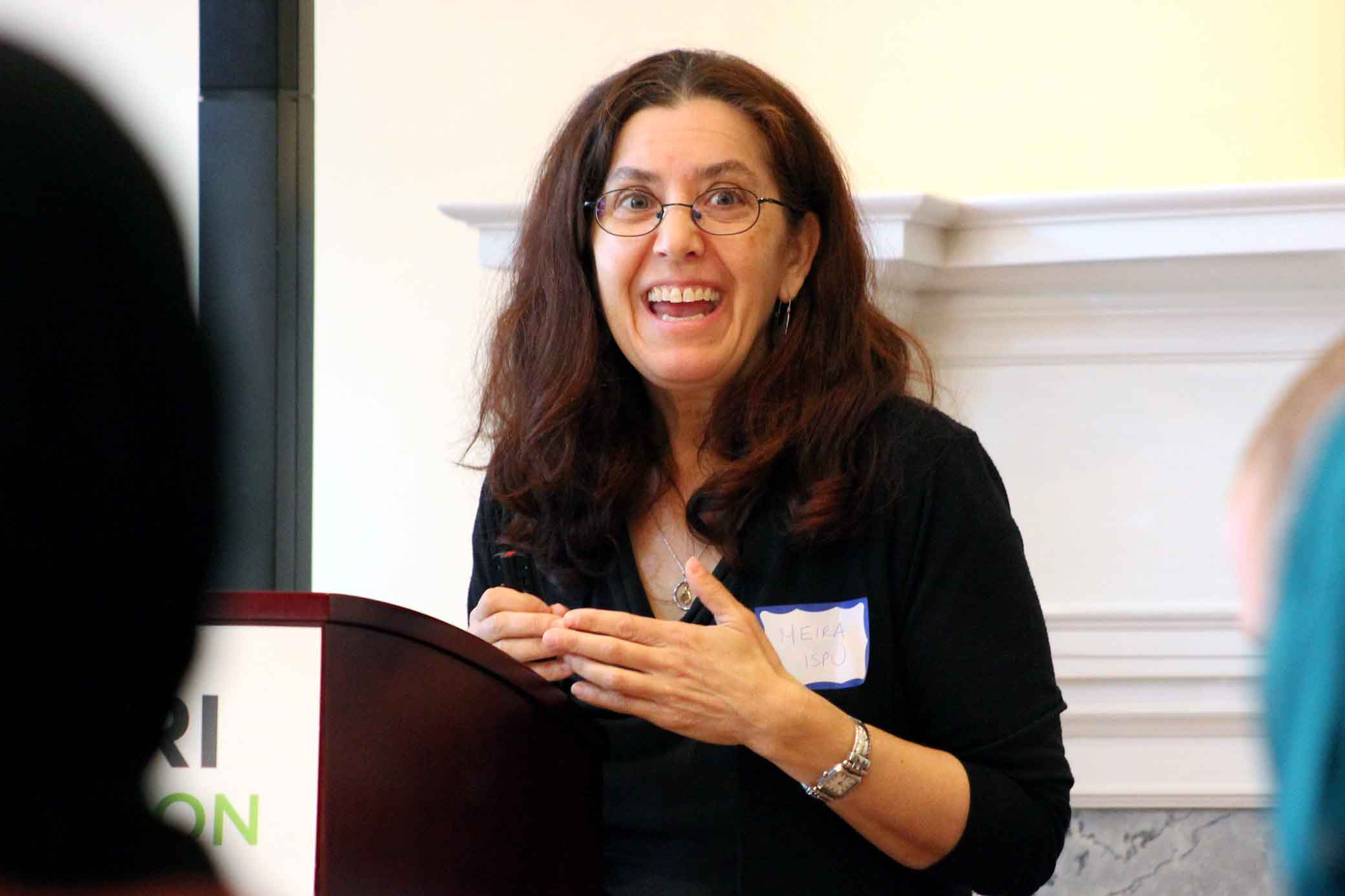 ISPU's executive director, Meira Neggaz, smiles while presenting in front of a group