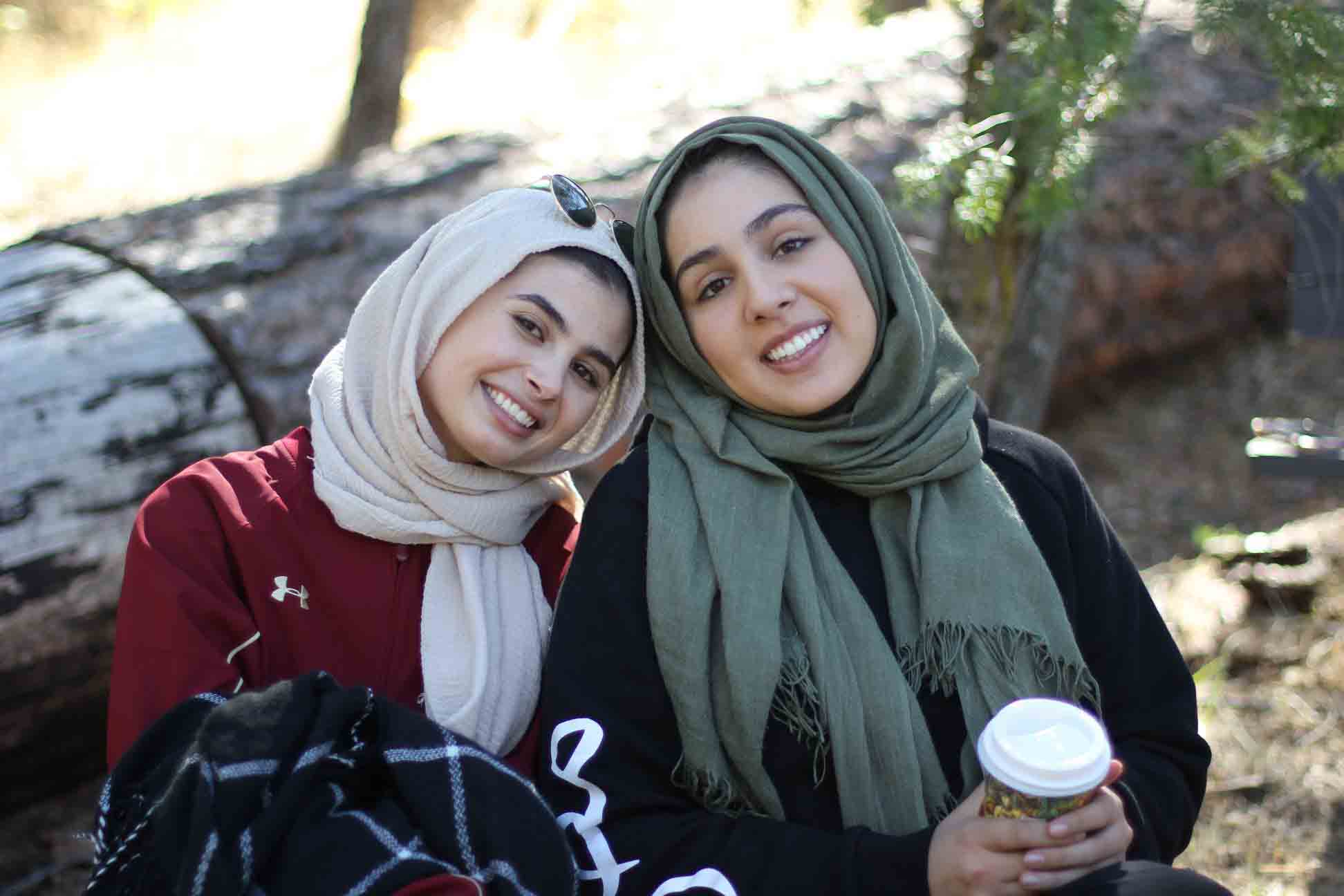 Two college-aged women wearing hijab smiling