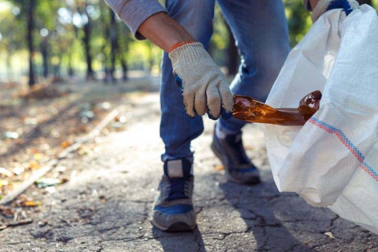 A man picks up a glass bottle and puts it in a white garbage bag in a park