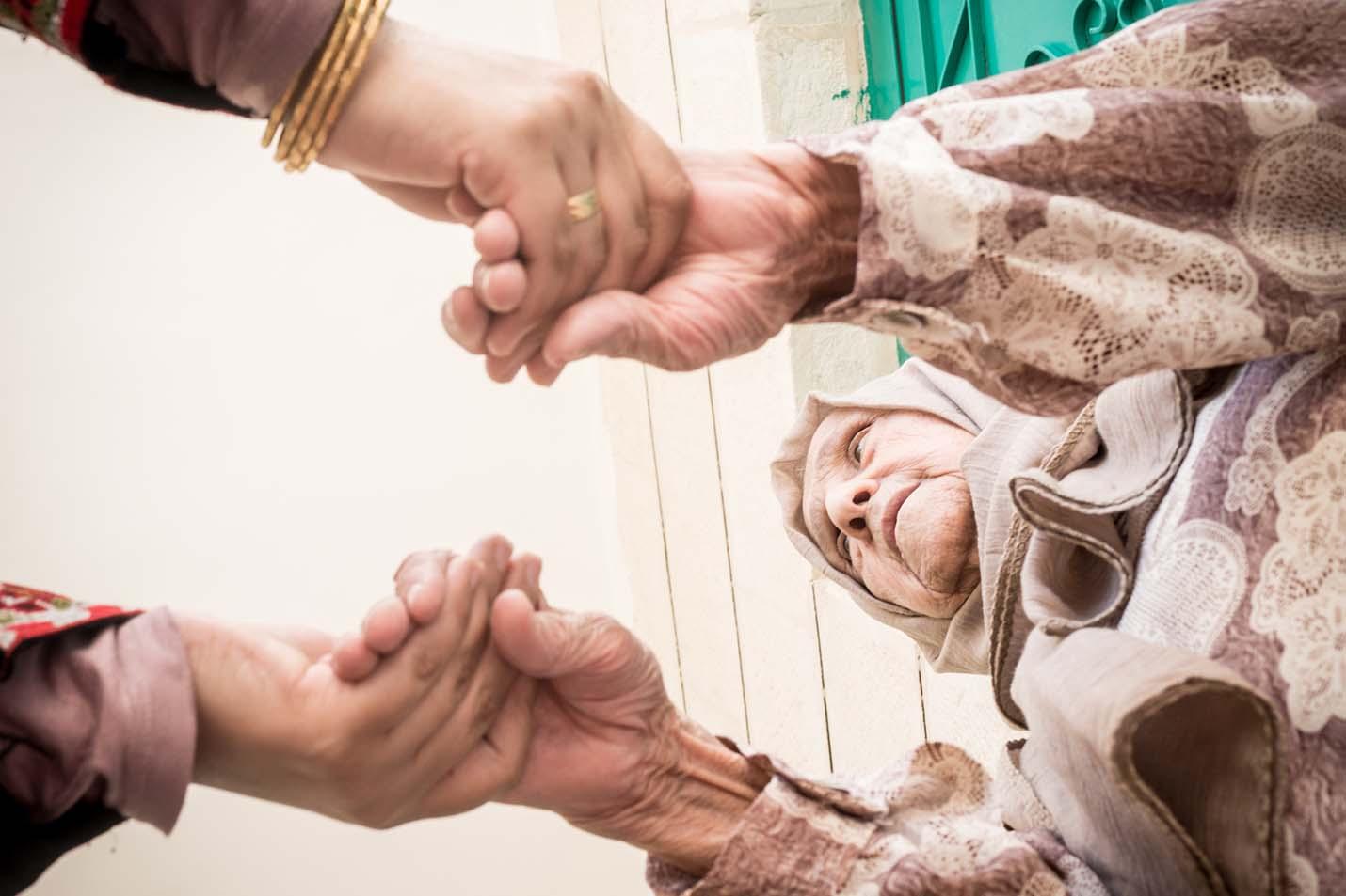 Muslim woman holding senior grandmother hands