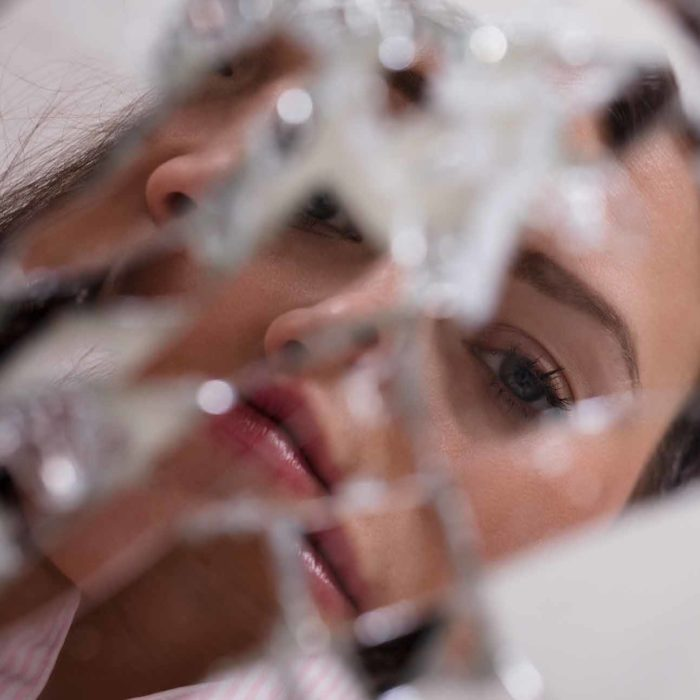 Reflection of a woman's face in a broken mirror