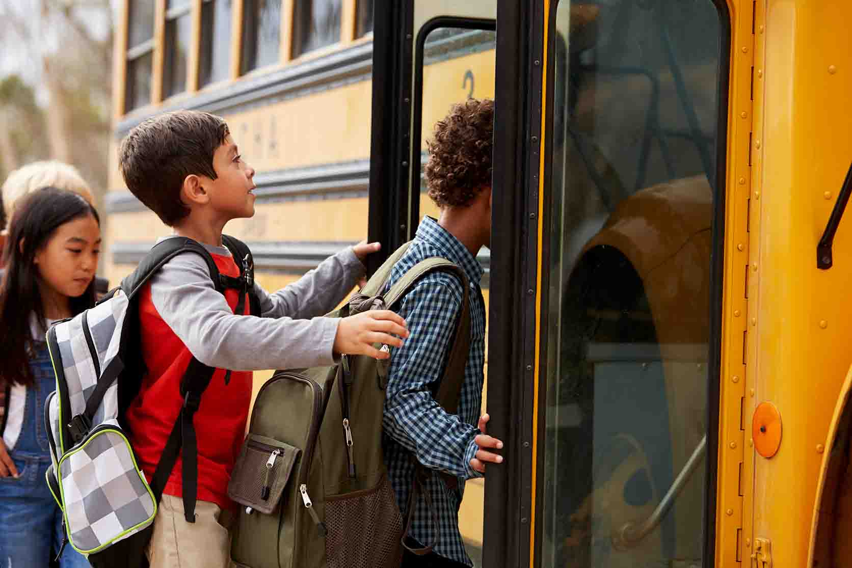 three young students boarding a school bus