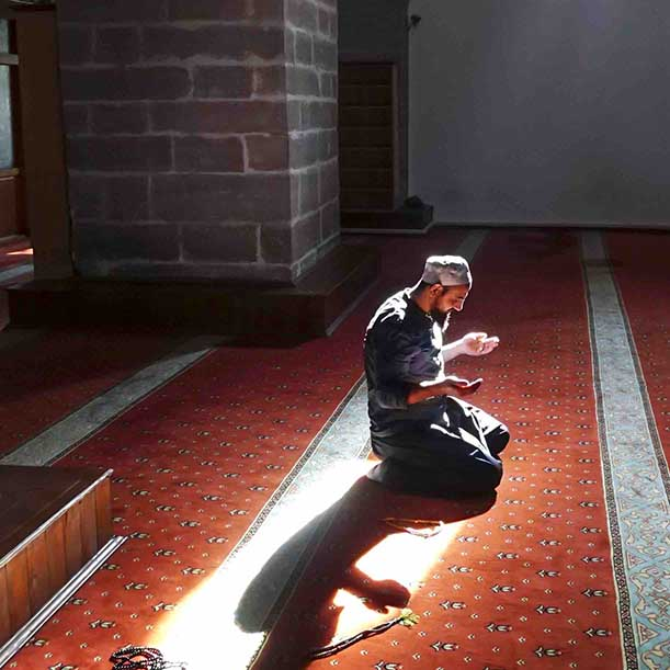 A Muslim man kneels in prayer alone at a mosque