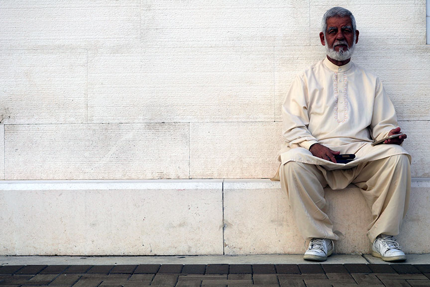 An older man with a beard sitting outside a mosque
