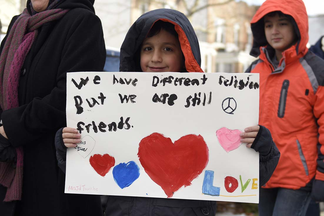 """A young boy at a rally carries a sign that says """"we have different religions, but we are still friends"""""""