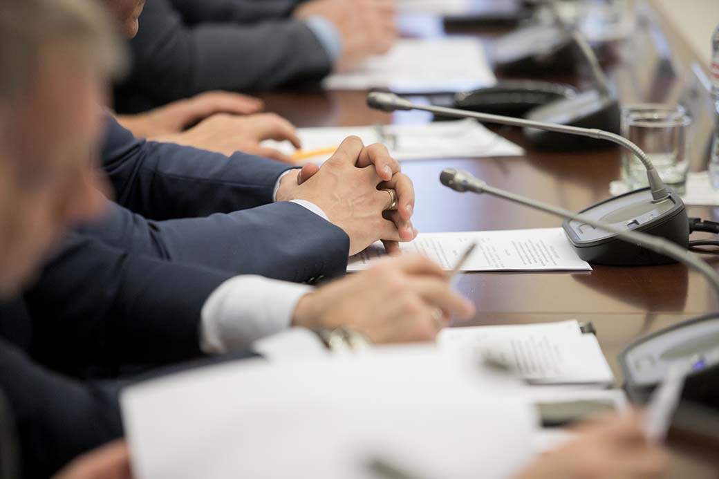 Politician sitting by table with his hands over document during political summit or conference