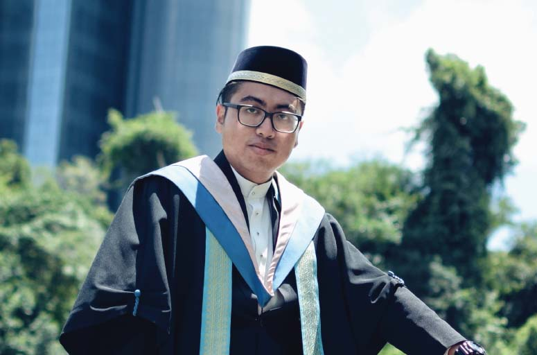 A man in graduation robes and glasses