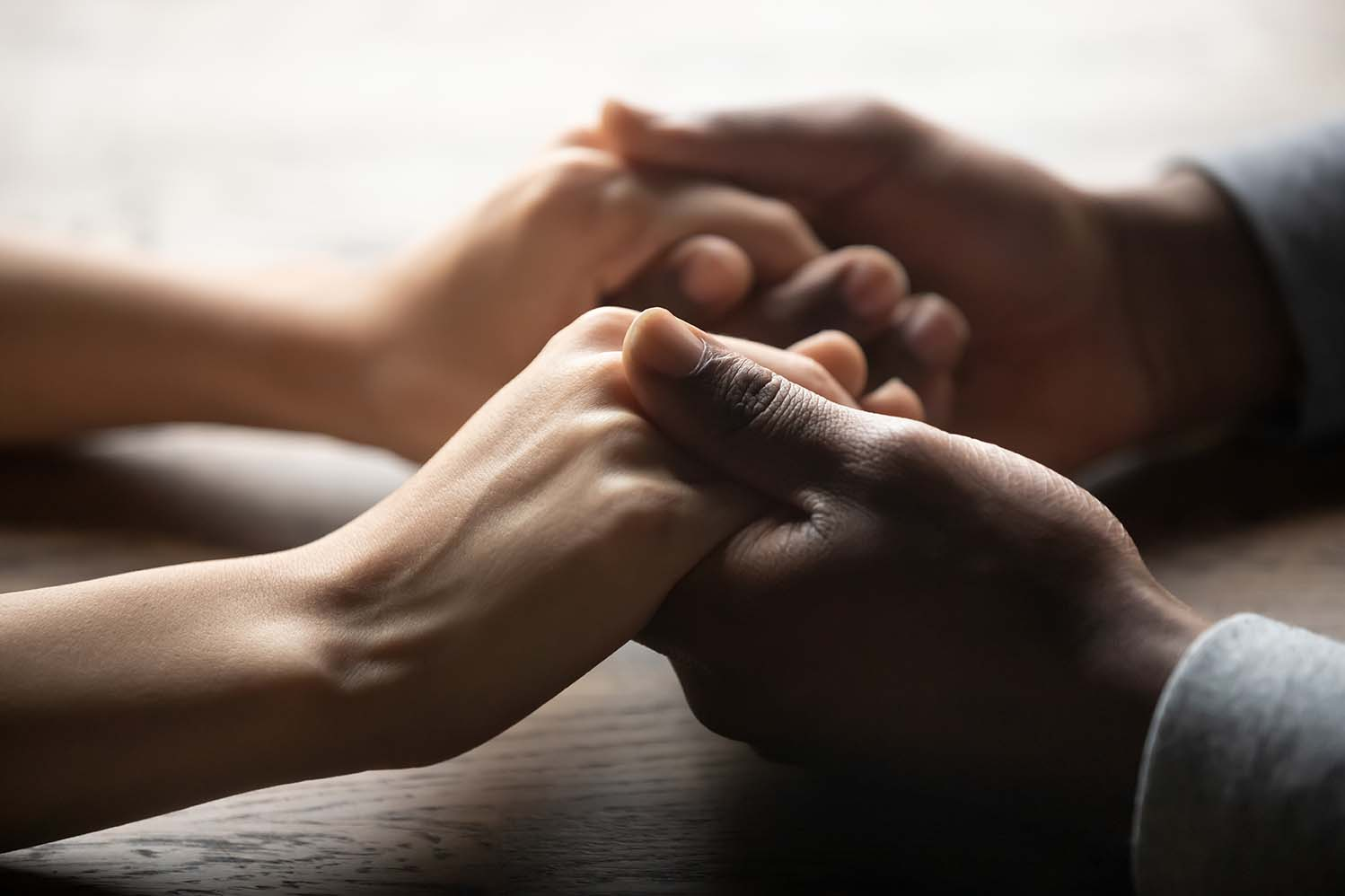 Mixed race couple holding hands on table