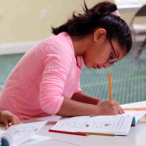 A young girl completes assignments in a workbook