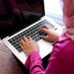 A girl in hijab typing on a laptop