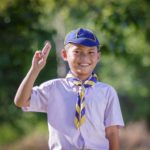 A cub scout raises his hand to say the pledge