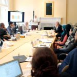 ISPU's first cohort of Educators gathered around a conference table for their training