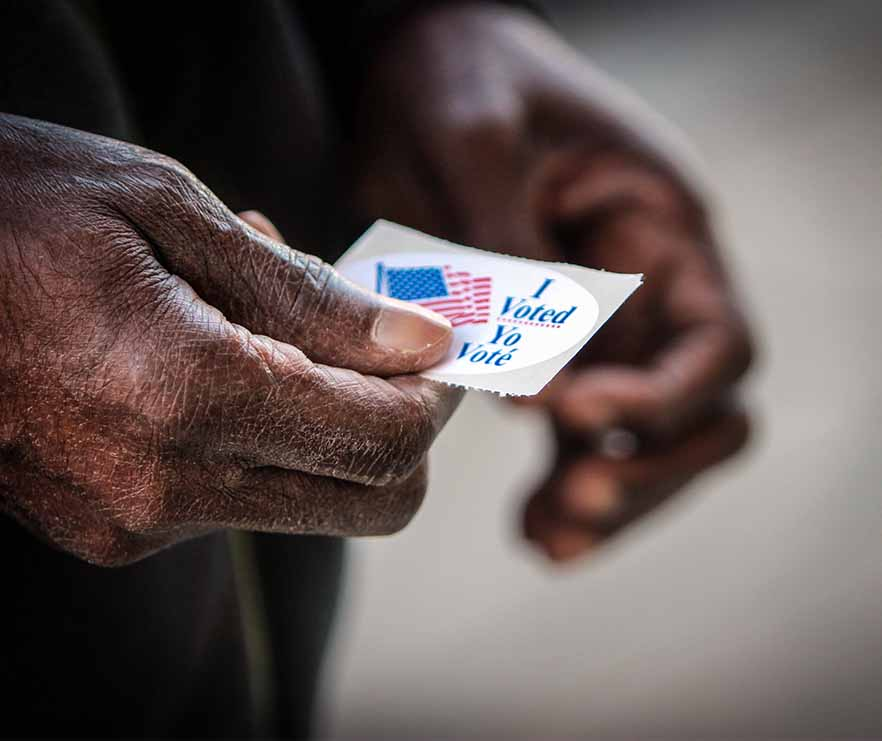 """An elderly African American man holds his """"I voted"""" sticker after he cast his ballot"""