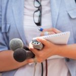 A journalist holds a notebook, a recorder, and two microphones