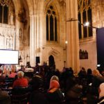A crowd watching a presentation in the cathedral of St. John the Divine in NYC