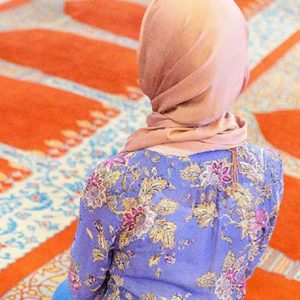 Woman wearing an orange hijab kneeling in a mosque